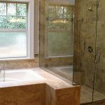 white bathtub surrounded with brown granite