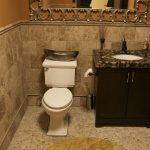 bathroom with beige floor and wall tiles and a black counter