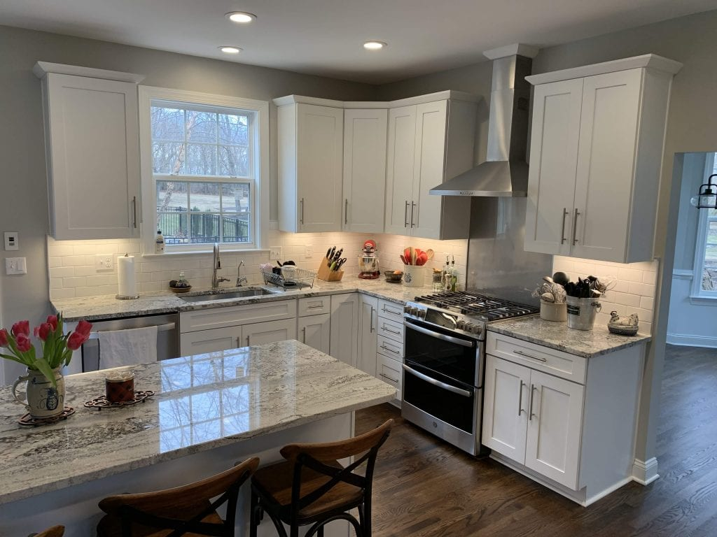 kitchen with black and white marbled counters and white cabinets